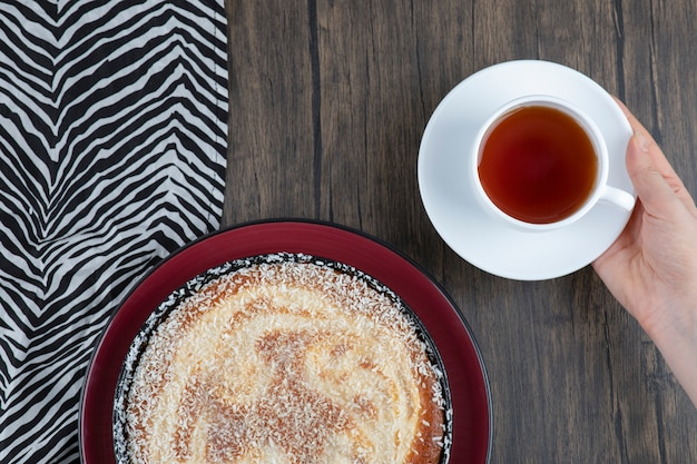 홍차 한잔과 함께 맛있는 파이 한 접시가 나무 테이블에 놓여 있습니다.