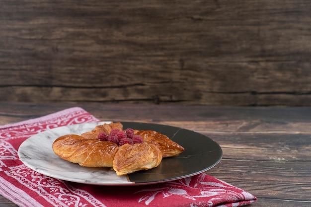 Тарелка вкусного малинового теста на деревянном столе.