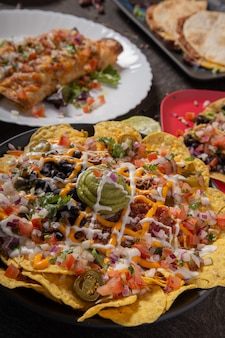 Тарелка вкусных тортильи начос с плавленым сырным соусом, мясным фаршем, перцем халапеньо, красным луком, зеленым луком, помидорами, черными оливками, сальсой и сметаной с радостью гуакамоле.