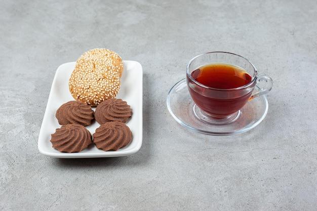 Тарелка различного печенья и чашка ароматного чая на мраморной поверхности
