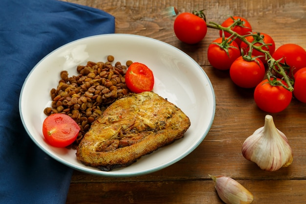 Тарелка рыбы с чечевицей и помидорами на круглой подставке с вилкой на синей салфетке рядом с помидорами черри и лимоном.