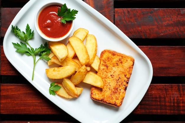 Тарелка картофеля-фри с наверстыванием, деревянный фон