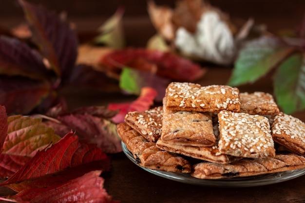 На столе, усеянном осенними листьями, стоит тарелка со свежим вкусным печеньем.