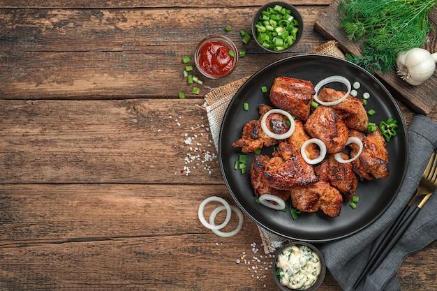 나무 배경에 양파와 신선한 허브를 곁들인 튀긴 고기 한 접시. 케밥, 바베큐. 상위 뷰, 복사 공간입니다.