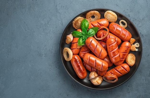 어두운 회색 배경에 양파, 마늘, 바질을 곁들인 튀긴 소시지 한 접시. 상위 뷰, 복사를 위한 공간입니다.
