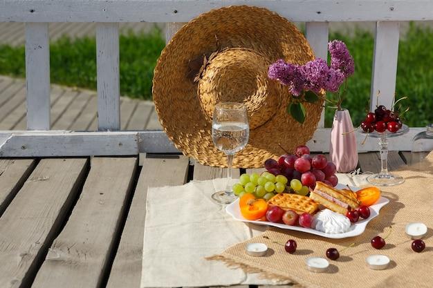 古い木の床の黄麻布の上に、果物のプレート、澄んだ水、ライラックの花の花瓶が立っています。