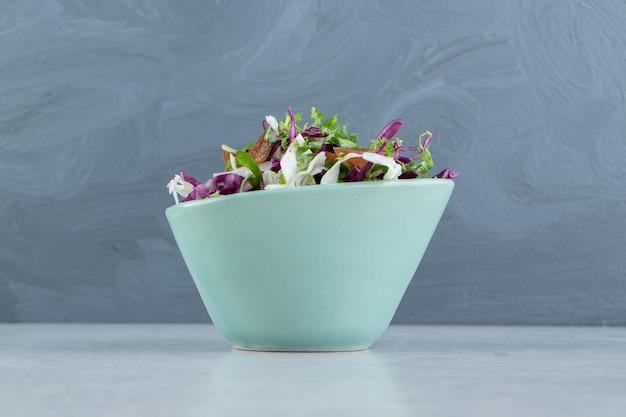 Тарелка тертых овощей с лимоном на мраморном фоне.
