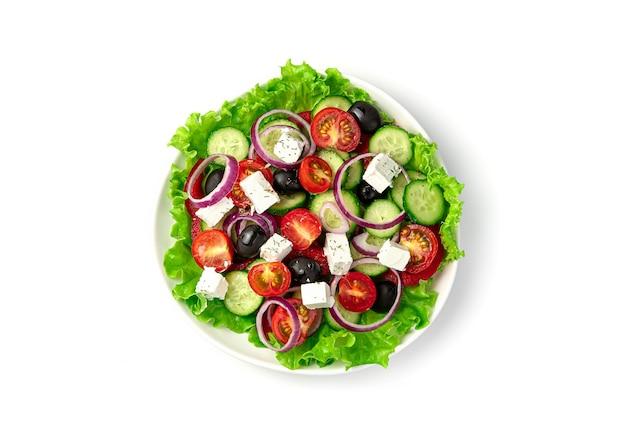 흰색 배경에 그리스 샐러드 접시. 평면도. 적절한 영양의 개념.