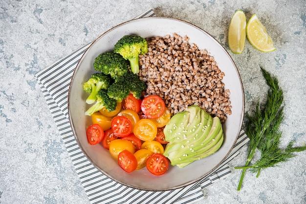 Тарелка здорового веганский салат на обед на сером фоне.