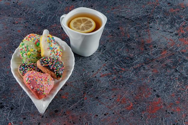 Тарелка печенья в форме сердца с посыпкой и чашка горячего чая Premium Фотографии
