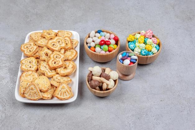 Тарелка самодельного печенья рядом с мисками конфет и шоколадных грибов на мраморном фоне. фото высокого качества