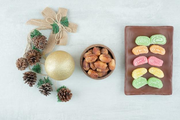 Тарелка мармелада и рождественский золотой шар на белом фоне. фото высокого качества