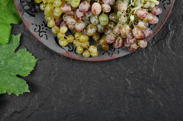 暗い背景に葉を持つ混合ブドウのプレート。高品質の写真