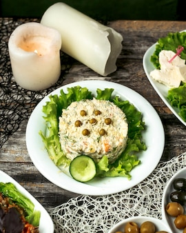 Тарелка оливкового салата с огурцом и листьями салата