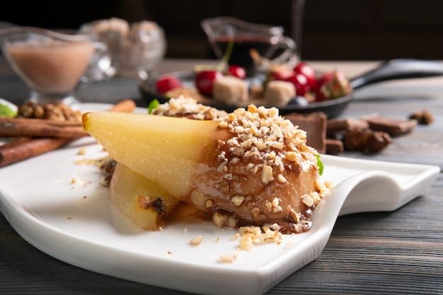 暗い木製のテーブルの上にワインソースと梨のデザートのプレート