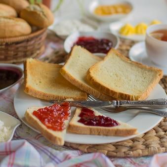 평평한 사각 토스트 조각과 잼이 든 삼각 토스트 한 접시
