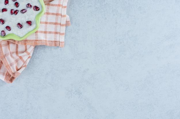 Тарелка каши на полотенце на мраморе.