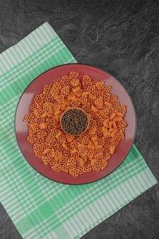 黒のテーブルにコショウとハートの形の生パスタのプレート