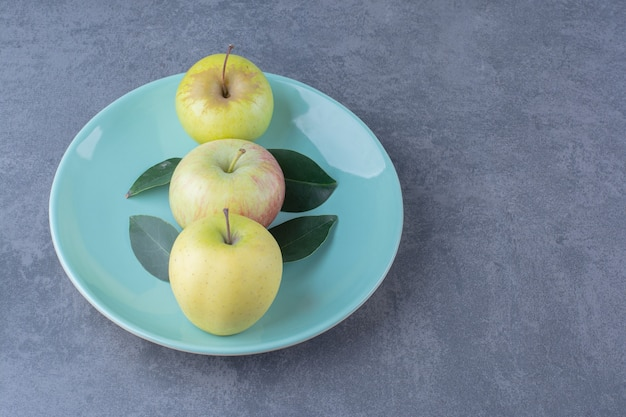 Тарелка спелых яблок и листьев на мраморном столе.