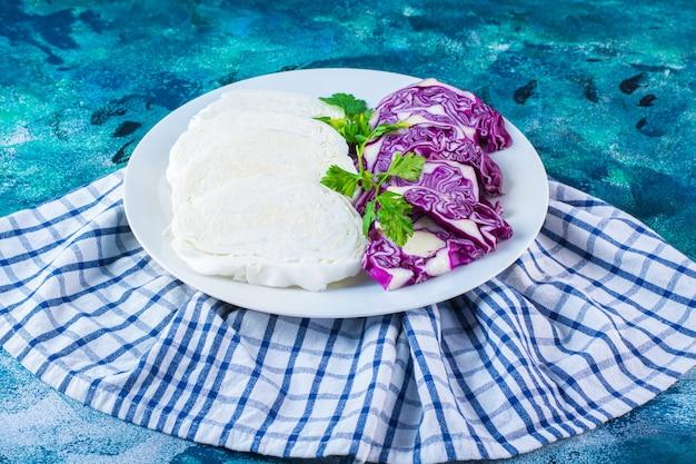 Тарелка нарезанной капусты и краснокочанной капусты на полотенце