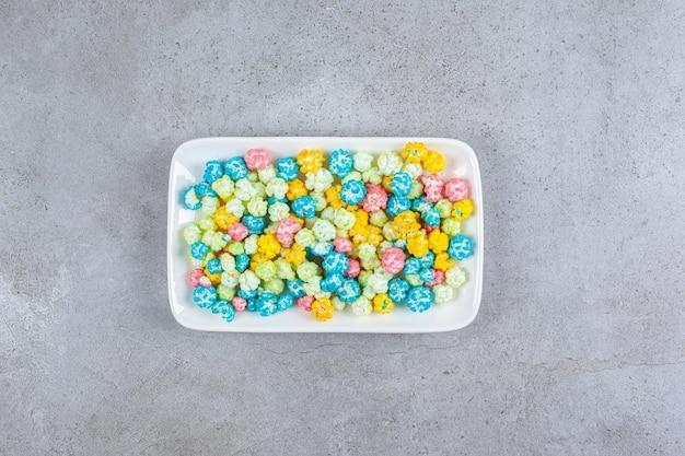Тарелка сладких конфет попкорна на мраморном фоне. фото высокого качества