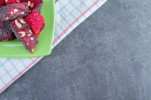 Тарелка рахат-лукумов на кухонном полотенце на мраморной поверхности