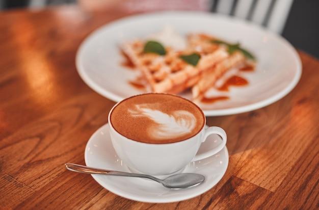 아늑한 카페의 나무 테이블에 캐러멜을 곁들인 웨이퍼 한 접시와 뜨거운 카푸치노 한 잔