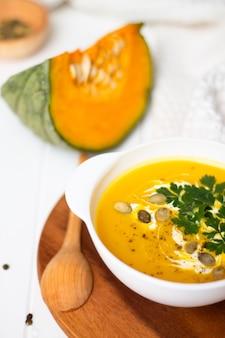 生姜生かぼちゃと木のスプーンの近くの白いテーブルにクリームハーブと種子と黄色のカボチャクリームスープのプレート垂直