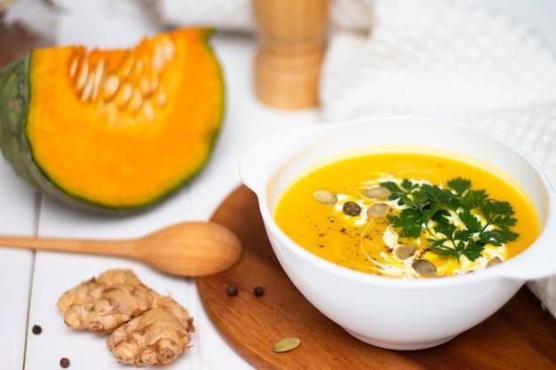 生姜生かぼちゃと木のスプーンの近くの白いテーブルにクリームハーブと種子と黄色のカボチャクリームスープのプレート