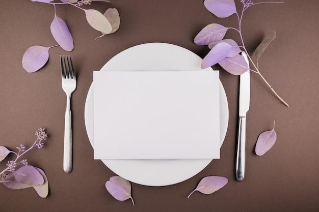 Тарелка на стол со столовыми приборами и декором из лепестков