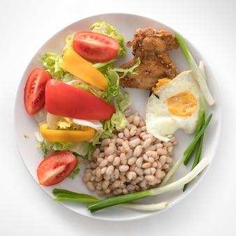 Тарелка со здоровым завтраком. фасоль, жареное куриное крылышко.