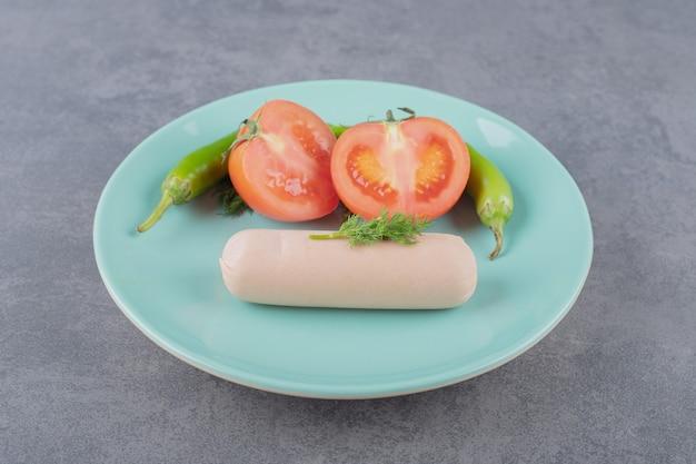 삶은 소시지와 얇게 썬 빨간 토마토를 곁들인 접시.