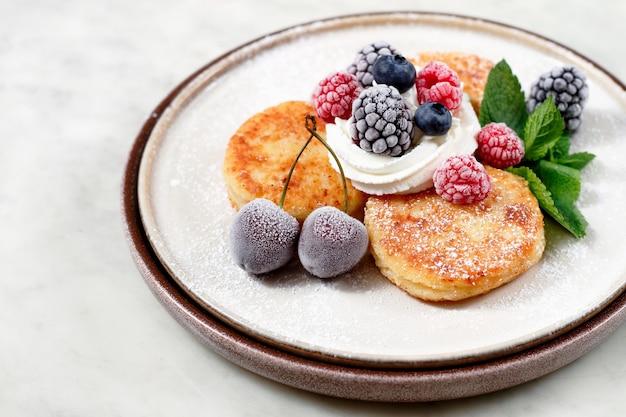 Тарелка с сырниками и ягодами