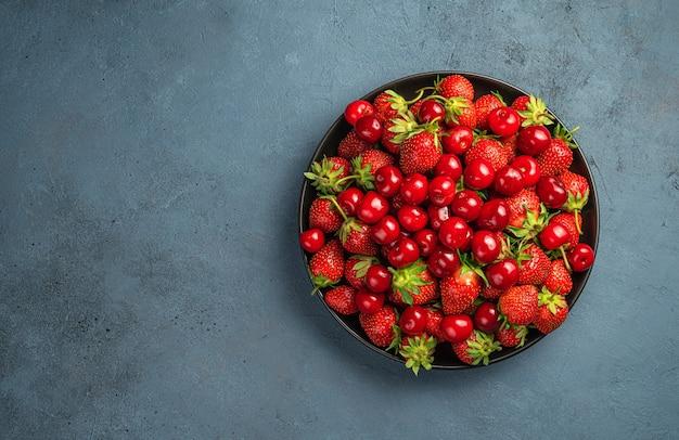 회색 파란색 배경에 체리와 딸기가 있는 접시. 평면도, 수평. 공간을 복사합니다.