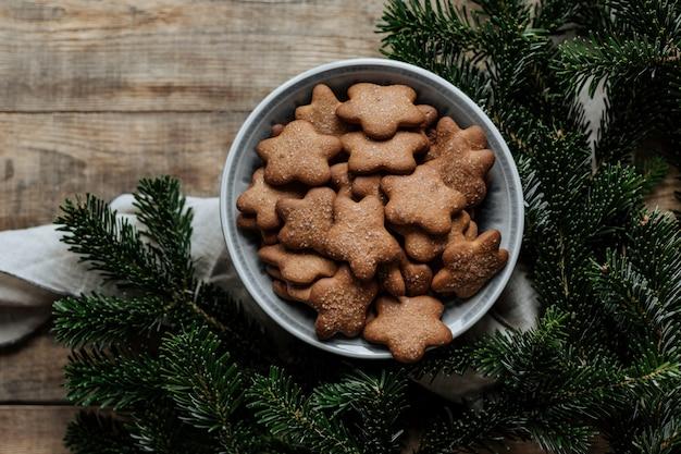 モミの枝の背景にクッキーとプレート。