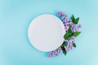 A plate with copy space around violet lilac on a blue background