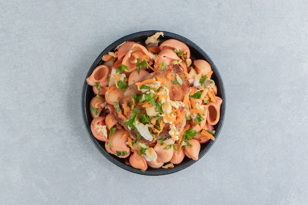 Тарелка с вкусными макаронами и жареным мясом.
