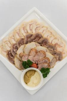 Тарелка с аппетитными кусочками нарезанной ветчины, колбаса, курица, мясное блюдо с выбором