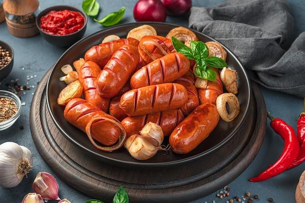 향신료, 후추, 마늘, 소스를 배경으로 튀긴 소시지를 곁들인 접시. 패스트 푸드. 측면 보기, 클로즈업입니다.