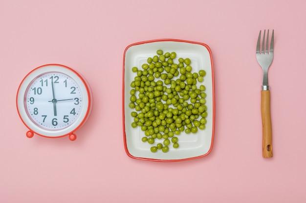 Тарелка с зеленым горошком, вилка и будильник на розовом фоне. концепция здорового питания для похудения.
