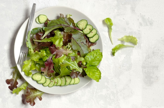 Тарелка с зелеными листьями салата, семенами кунжута и дольками огурца, слева вилка