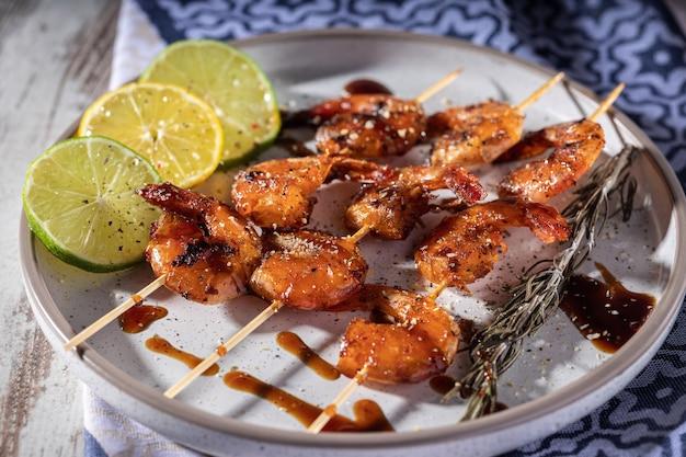 自家製エビフライの串焼きにニンニク、レモン、ハーブを添えたプレート、セレクティブフォーカス