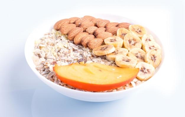 Muesli, 아몬드, 바나나, 감 흰색 배경에 고립 된 접시.