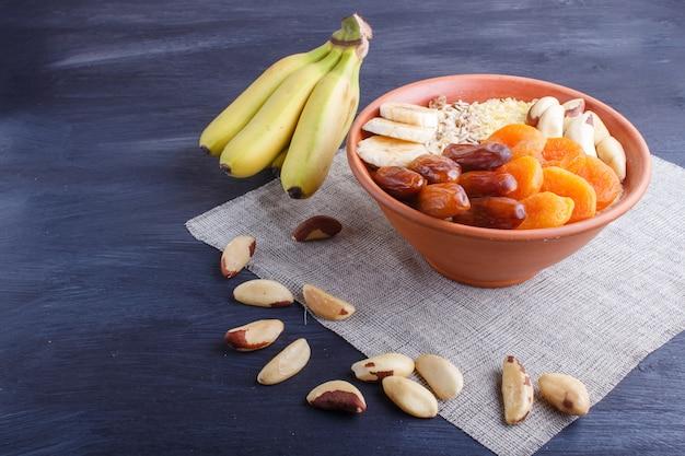 Muesli, 바나나, 말린 살구, 날짜, 검은 나무 배경에 브라질 너트와 접시.