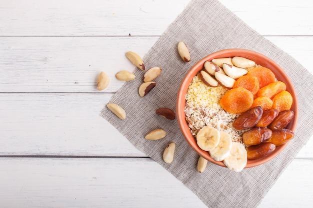 Muesli, 바나나, 말린 살구, 날짜, 흰색 나무 배경에 브라질 너트와 접시.