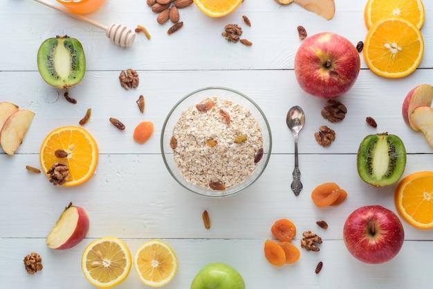 Тарелка с мюсли в окружении яблок, киви, сухофруктов, апельсинов и яблок. концепция здорового питания.