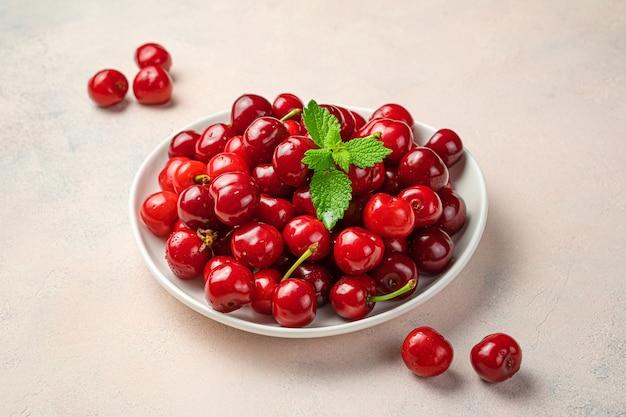 밝은 분홍색 배경에 잘 익은 체리가 있는 접시. 측면 보기, 수평. 여름 과일.