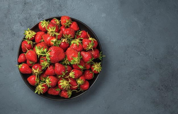 진한 파란색 배경에 익은 딸기와 접시. 상위 뷰, 복사 공간입니다.