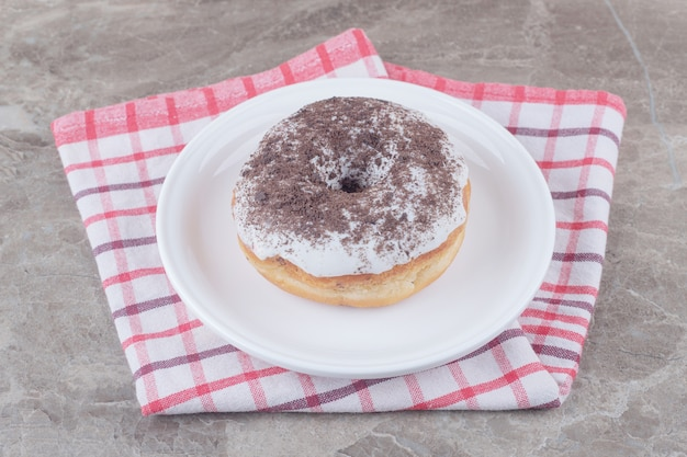 Блюдо с пончиком на полотенце на мраморе