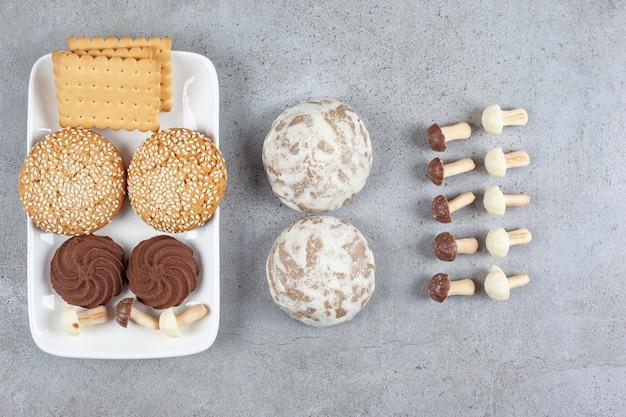 Блюдо с печеньем и рядом с ним. с выстроенными шоколадными грибами на мраморном фоне. фото высокого качества